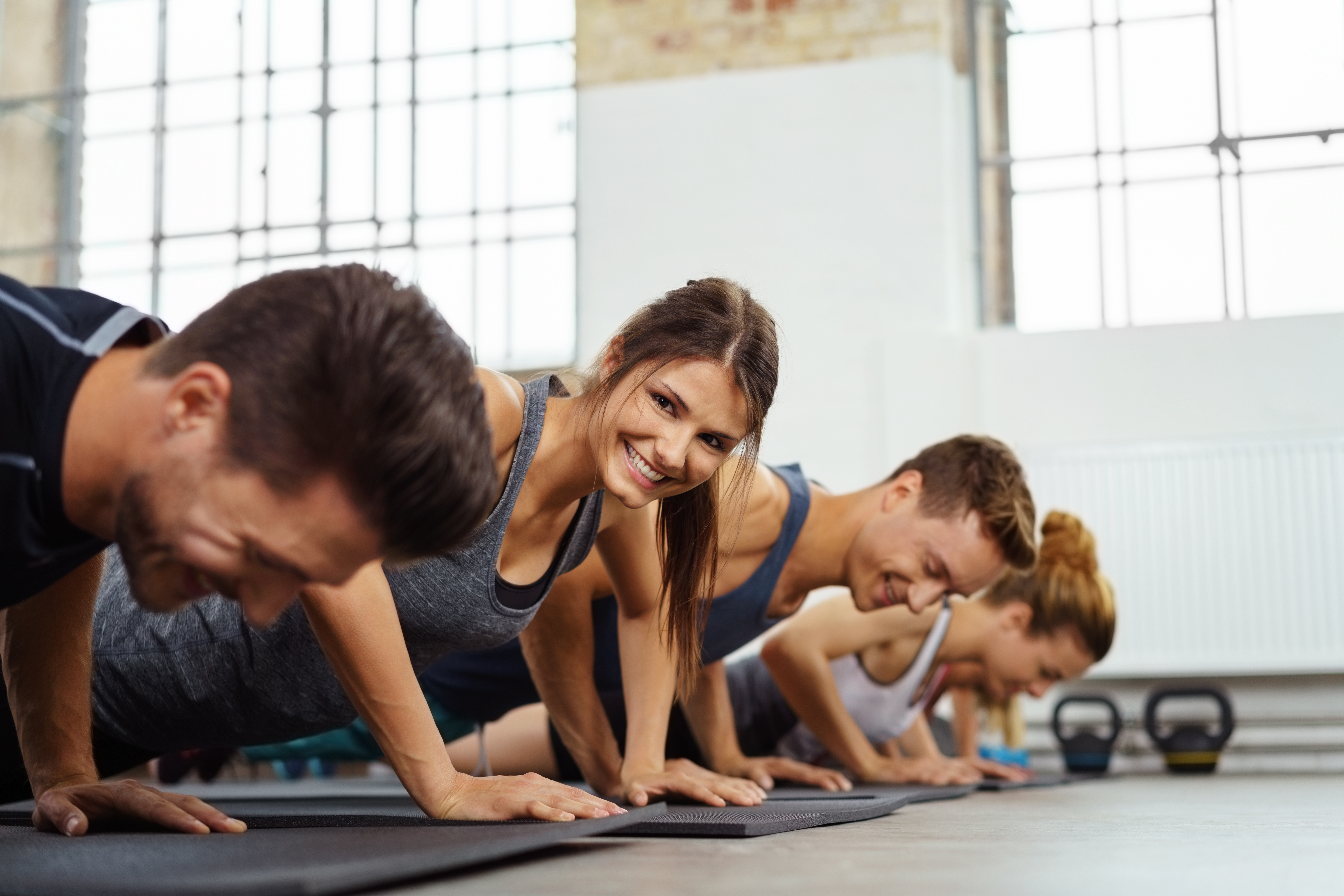 Woman doing push ups smiles at camera