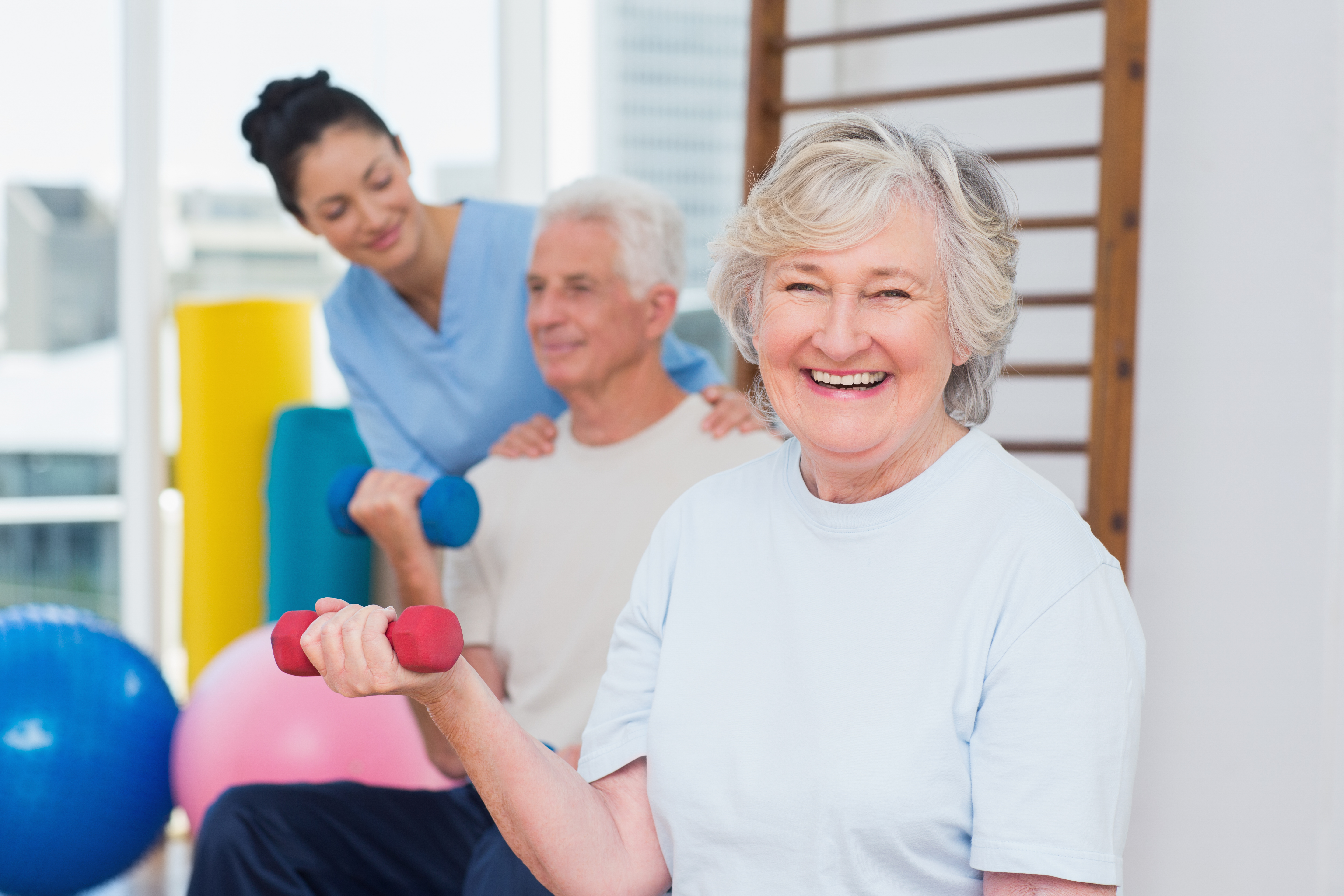 Portrait of happy senior woman lifting dumbbells while sitting with man and instructor in gym
